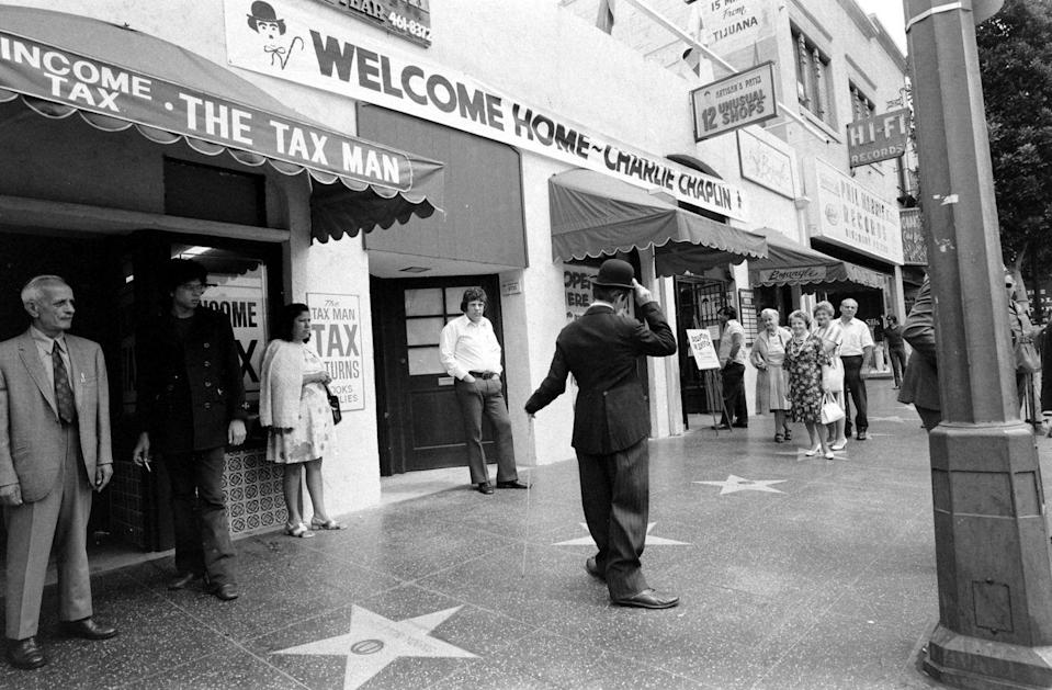 <p>Charlie Chaplin poses near his star on the Walk of Fame. </p>