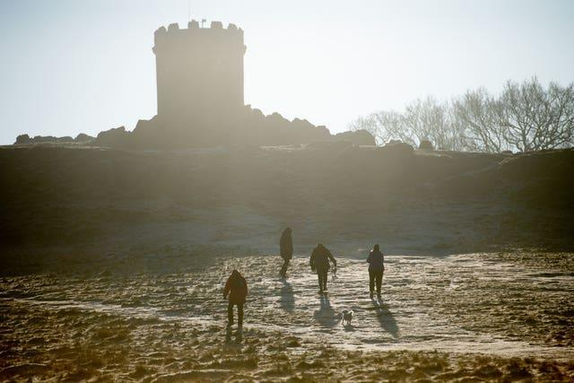 Walkers approach Old John Tower at Bradgate Park in Leicester, on a cold and bright morning across the Midlands