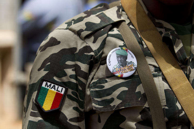 A soldier wears a button bearing the image of coup leader Capt. Amadou Haya Sanogo with the words 'President, CNRDRE,' the French acronym by which the ruling junta is known, as he stands guard at junta headquarters in Kati, outside Bamako, Mali Sunday, April 1, 2012. The leader of Mali's recent coup says he is reinstating the nation's previous constitution amid international pressure to restore constitutional order.(AP Photo/Rebecca Blackwell)
