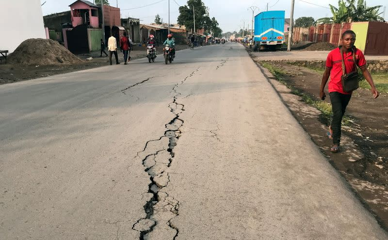 A pedestrian walks near a crack on the road caused by earth tremors as aftershocks following the eruption of Mount Nyiragongo volcano near Goma