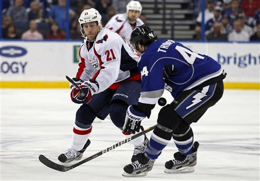 Washington Capitals' Brooks Laich, left, looks to dump the puck past Tampa Bay Lightning's Nate Thompson during the first period of an NHL hockey game, Saturday, Feb. 18, 2012, in Tampa, Fla. (AP Photo/Mike Carlson)