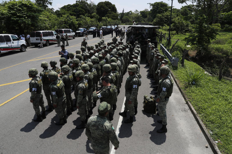 Military Police form up on the highway, in Metapa, Chiapas state Mexico, Wednesday, June 5, 2019. A law enforcement group of police officers, Marines, Military Police and immigration officials arrived at the area to intercept a caravan of migrants that had earlier crossed the Mexico – Guatemala border. (AP Photo/Marco Ugarte)