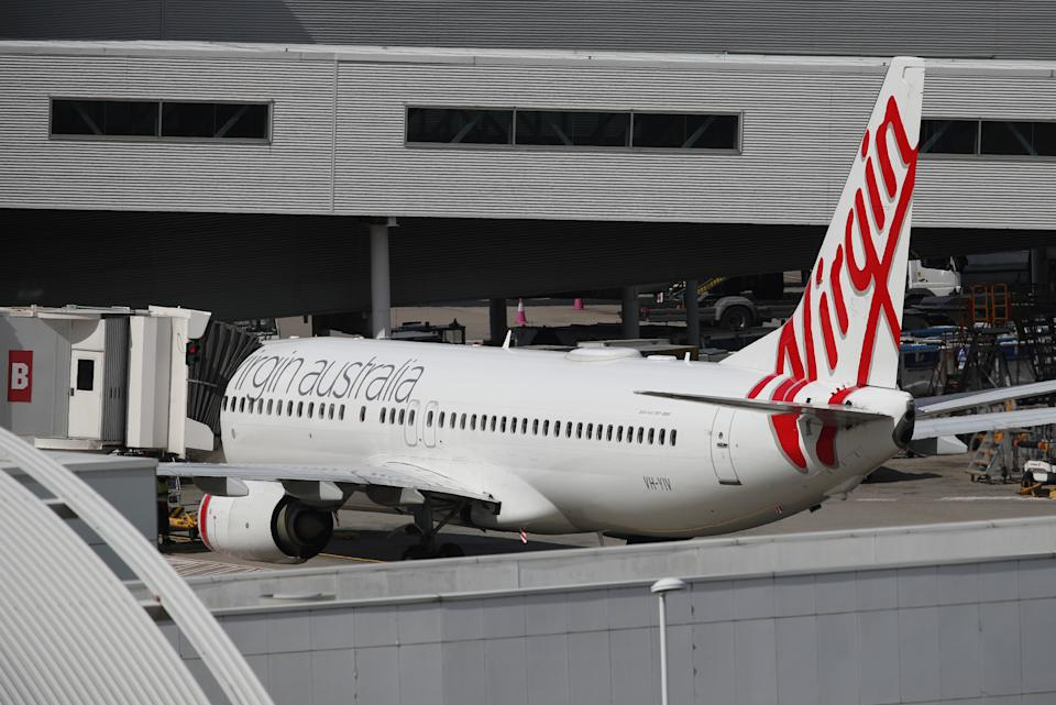A Virgin Australia Airlines plane is seen at Kingsford Smith International Airport the morning after Australia implemented an entry ban on non-citizens and non-residents intended to curb the spread of the coronavirus disease (COVID-19) in Sydney, Australia, March 21, 2020.  REUTERS/Loren Elliott