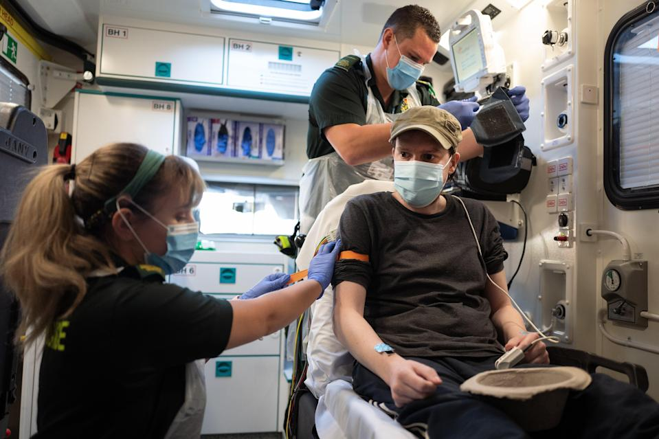 <p>Paramedics treat a patient who tested positive for Covid-19</p> (Getty)