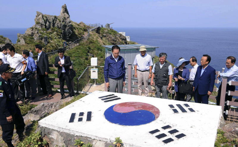 South Korean President Lee Myung-bak, center, looks at a national flag upon his arrival at islands called Dokdo in Korea and Takeshima in Japan Friday, Aug. 10, 2012. Lee made a surprise visit Friday to islets at the center of a long-running territorial dispute with Japan, ignoring warnings from Tokyo that it would worsen the neighbors' already strained relations.(AP Photo/Korea Pool)  KOREA OUT