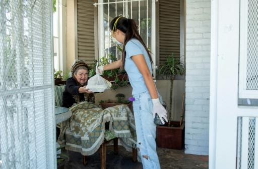 """Mira Kwon, the 16 year-old high school student who launched the Los Angeles branch of """"Zoomers to Boomers"""", delivers groceries to Mary Navarro, an elderly disabled woman -- the service is now available in more than a dozen US cities"""