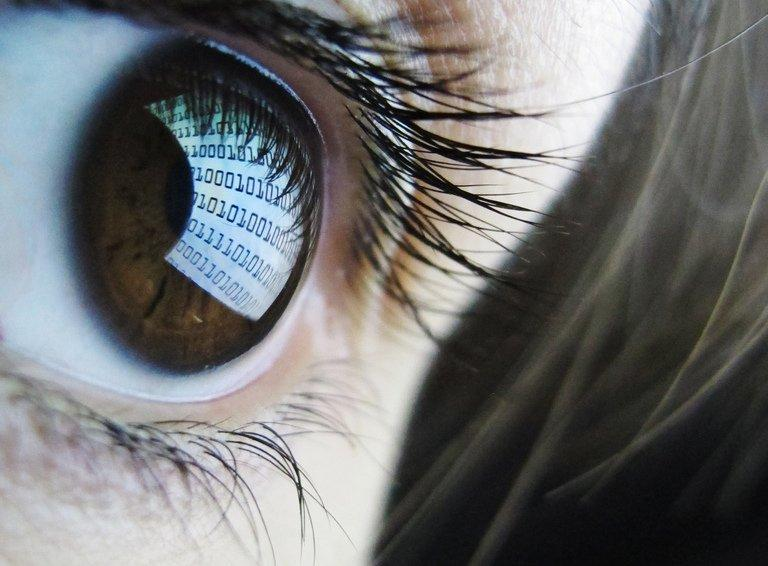 A binary code is reflected from a computer screen in a woman's eye on October 22, 2012