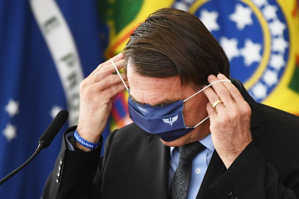 Brazilian President Jair Bolsonaro puts a face mask on during the launching of the Brazilian Waters Program in celebration of International Water Day at Planalto Palace in Brasilia, on March 22, 2021. (Photo by EVARISTO SA / AFP) (Photo by EVARISTO SA/AFP via Getty Images)