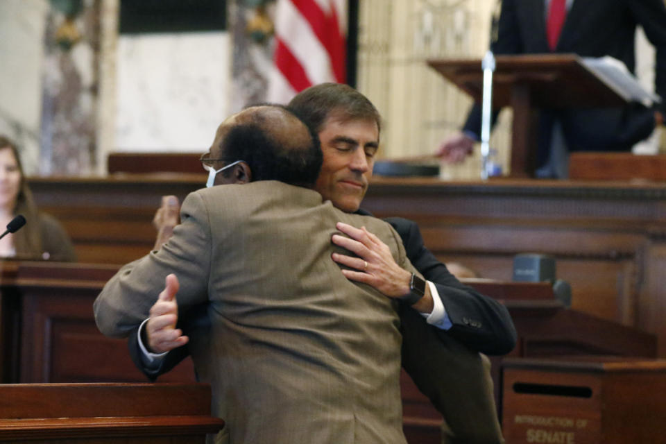 Sen. Briggs Hopson, R-Vicksburg, is hugged by Sen. Albert Butler, back to camera, D-Port Gibson, after the Senate voted to change the state flag Sunday, June 28, 2020, at the Capitol in Jackson, Miss. Hopson presented the bill to the body. Mississippi lawmakers voted to surrender the Confederate battle emblem from their state flag. Republican Gov. Tate Reeves has said he will sign the bill, and the state flag would lose its official status as soon as he signs the measure. (AP Photo/Rogelio V. Solis)