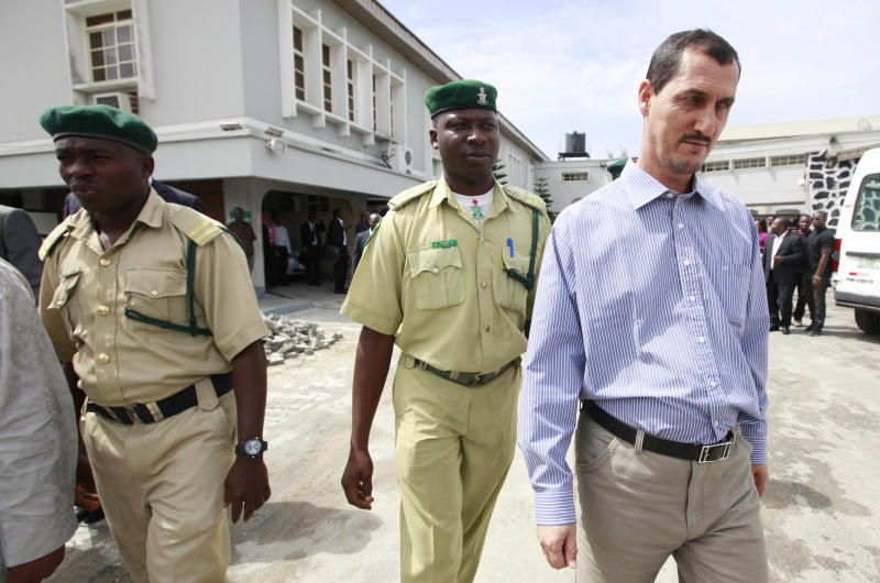 Azim Aghajani, right, an Iranian citizen, charged with orchestrating an illegal arms shipment into Nigeria from Iran is led away, after sentencing, at the Federal High Court, in Lagos, Nigeria, Monday, May 13, 2013. . An Iranian and his Nigerian accomplice were sentenced to five years in prison Monday over a plot they orchestrated to smuggle a shipment of military-grade weapons including mortar rounds into West Africa. Both Azim Aghajani and his accomplice Usman Abbas Jega pleaded for leniency in the hearing, which saw Justice Okechukwu J. Okeke avoid giving the men a maximum sentence of life in prison. The two men already have served more than two years in prison waiting for trial, time which will count toward their release. (AP Photos/Sunday Alamba)