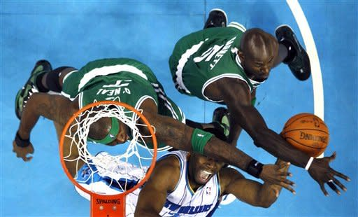New Orleans Hornets power forward Carl Landry (24) goes to the basket as Boston Celtics center Jermaine O'Neal (7) and power forward Kevin Garnett (5) defend during the first half of an NBA basketball game in New Orleans, Wednesday, Dec. 28, 2011. (AP Photo/Gerald Herbert)