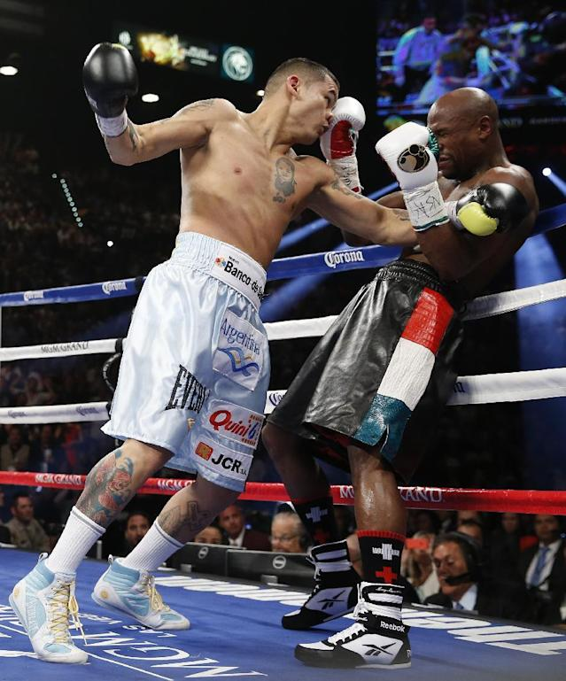 Marcos Maidana, left, from Argentina, drives Floyd Mayweather Jr. against the ropes in their WBC-WBA welterweight title boxing fight Saturday, May 3, 2014, in Las Vegas. (AP Photo/Eric Jamison)