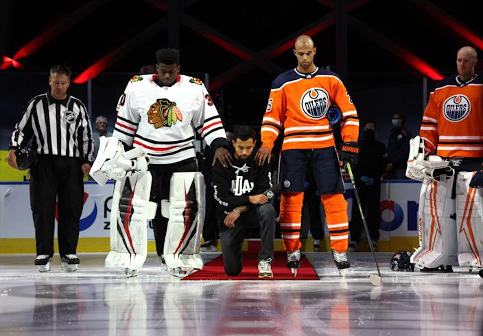 EDMONTON, ALBERTA - AUGUST 01: Malcolm Subban #30 of the Chicago Blackhawks and Darnell Nurse #25 of the Edmonton Oilers place their hands on Mathew Dumba of the Minnesota Wild during the national anthem of the United States before Game One of the Western Conference Qualification Round between the Edmonton Oilers and the Chicago Blackhawks at Rogers Place on August 01, 2020 in Edmonton, Alberta. (Photo by Dave Sandford/NHLI via Getty Images)