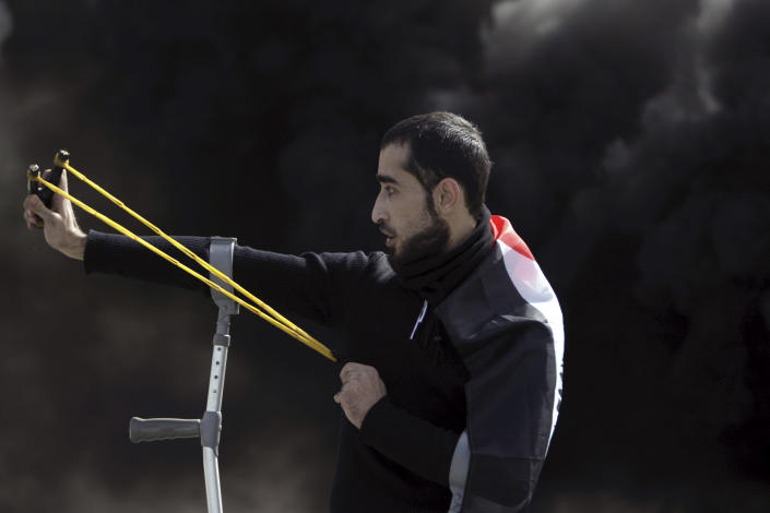 A Palestinian man aims a sling shot at Israeli soldiers during clashes north of the West Bank city of Jenin after a rally in support of the Palestinian prisoners in Israeli jails, Sunday, Feb. 24, 2013. The death of a 30-year-old Palestinian after interrogation by Israel's Shin Bet security service stokes new West Bank clashes, along with Israeli fears of a third Palestinian uprising. (AP Photo/Mohammed Ballas)