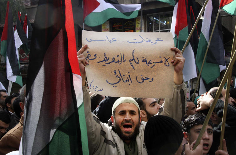 "FILE - In this Friday, Jan. 28, 2011 file photo, a Palestinian man shouts slogans as he carries a banner that reads in Arabic, ""Erekat, Abbas, no legitimacy for you to give up my right and my children right,"" during a rally against Palestinian President Mahmoud Abbas and his government, in the Palestinian refugee camp of Yarmouk near Damascus, Syria.  Since the start of the unrest, Syria's half million Palestinians have struggled to remain on the sidelines, saying they have little to gain and much to lose by taking sides in the fight between President Bashar Assad's regime and the armed rebels seeking to end his family's 40-year rule. (AP Photo/Bassem Tellawi, File)"