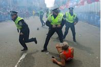 <p>Police officers with their guns drawn hear a second explosion near the finish line of the 117th Boston Marathon. The first explosion knocked down 78-year-old marathoner Bill Iffrig. </p>