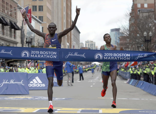 Lawrence Cherono, of Kenya, hits the tape to win the 123rd Boston Marathon in front of Lelisa Desisa, of Ethiopia, right, on Monday, April 15, 2019, in Boston. (AP Photo/Winslow Townson)