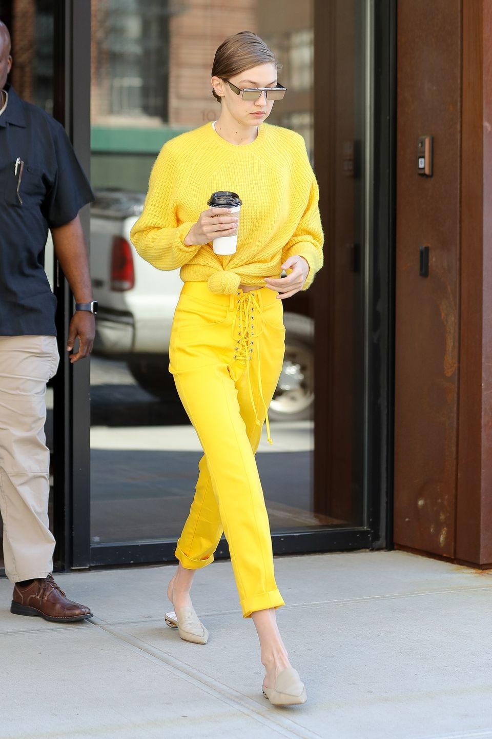 <p>In a bright yellow knotted pullover with matching lace-up pants and nude mules out in New York City. </p>