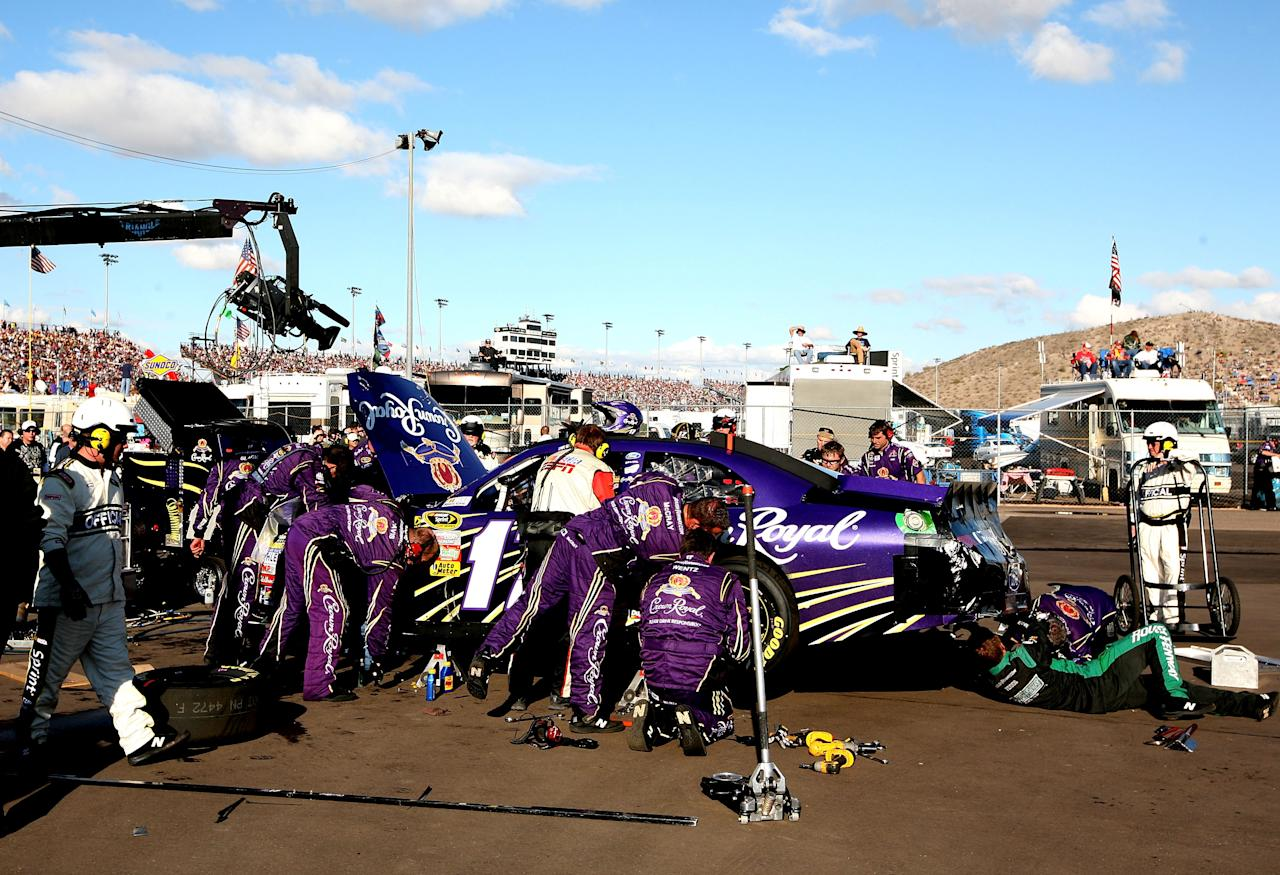 AVONDALE, AZ - NOVEMBER 13:  Crew members work on the car of Matt Kenseth, driver of the #17 Crown Royal Ford, after crashing with Brian Vickers, driver of the #83 Red Bull Toyota, during the NASCAR Sprint Cup Series Kobalt Tools 500 at Phoenix International Raceway on November 13, 2011 in Avondale, Arizona.  (Photo by Jerry Markland/Getty Images for NASCAR)