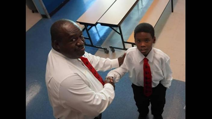 Holmes Elementary School math teacher Abe Coleman with one of the students he had mentored as part of his leadership role with the 5000 Role Models of Excellence Program at the Liberty City School.