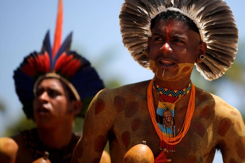 FILE PHOTO: Indigenous people from ethnic groups Pataxo and Tupinamba attend a protest to defend indigenous land, outside Brazil's Supreme Federal Court in Brasilia