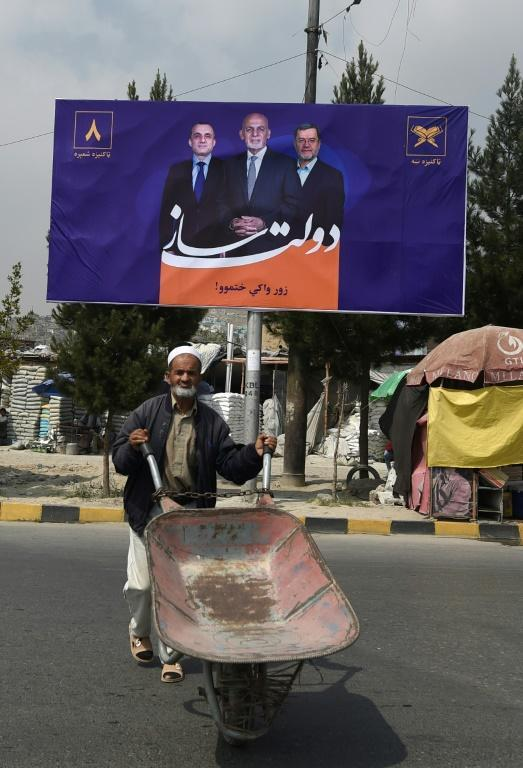 A Kabul resident pushes a wheelbarrow past a billboard depicting Afghanistan's President Ashraf Ghani (C), on the first day of the presidential election campaign