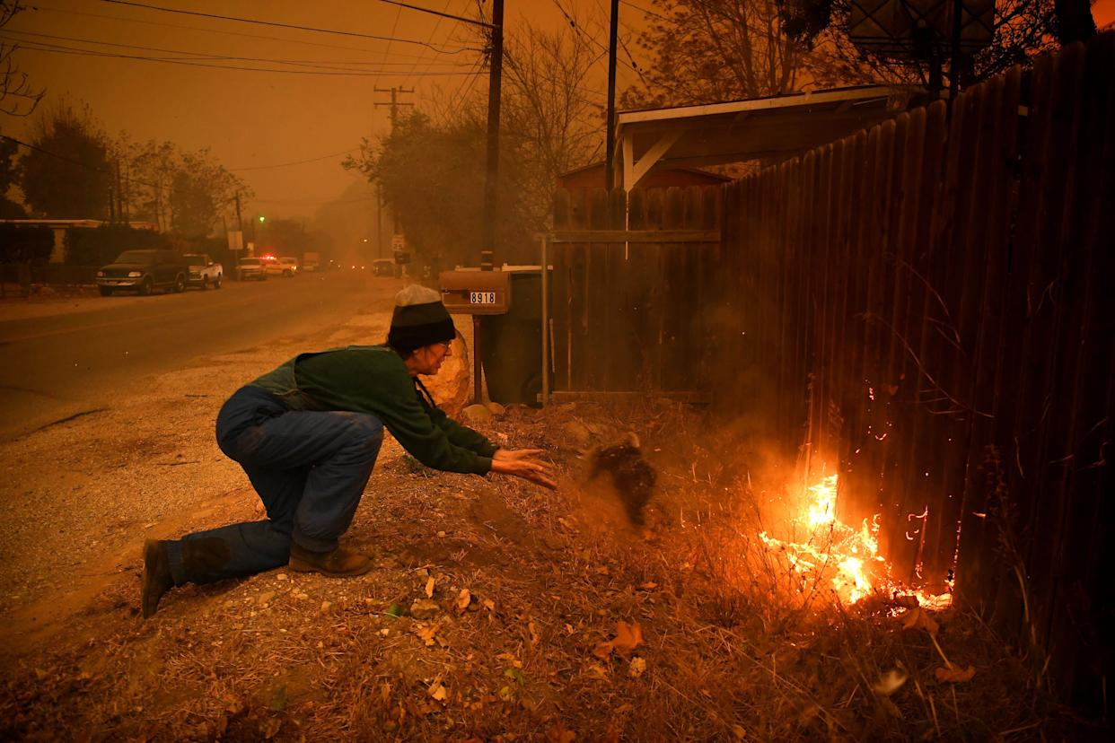 Carolyn Potter tries to save her house from the flames as she throws dirt on her fence in Ventura County's Casita Springs community.