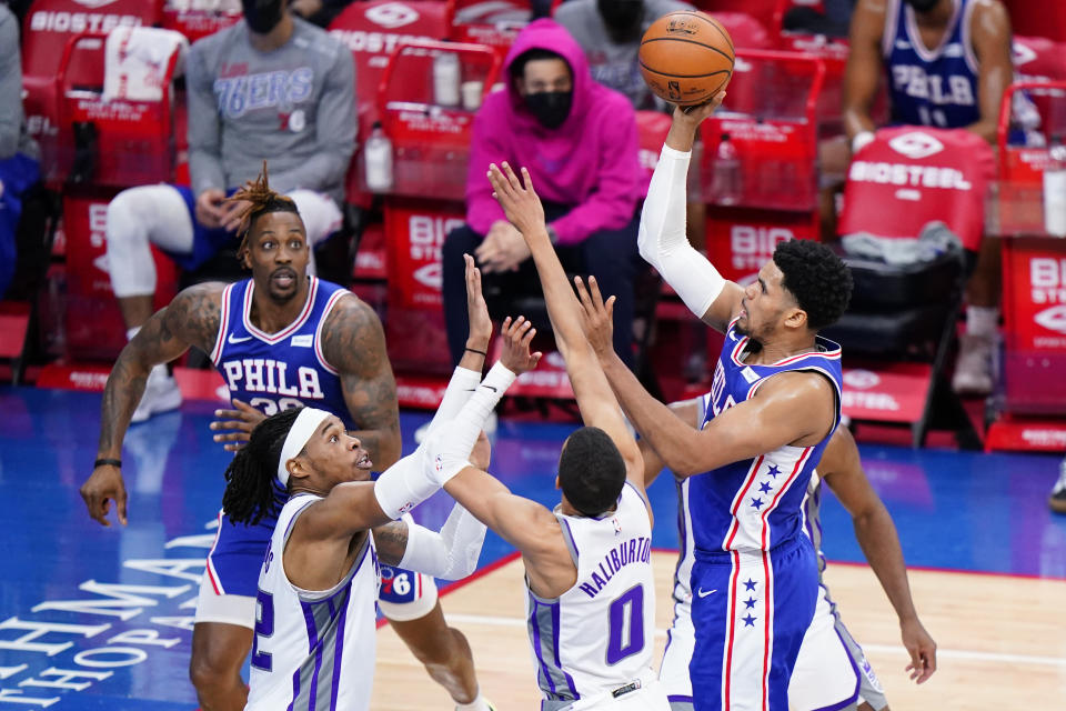 Philadelphia 76ers' Tobias Harris, from right, goes up for a shot against Sacramento Kings' Tyrese Haliburton and Richaun Holmes during the first half of an NBA basketball game, Saturday, March 20, 2021, in Philadelphia. (AP Photo/Matt Slocum)
