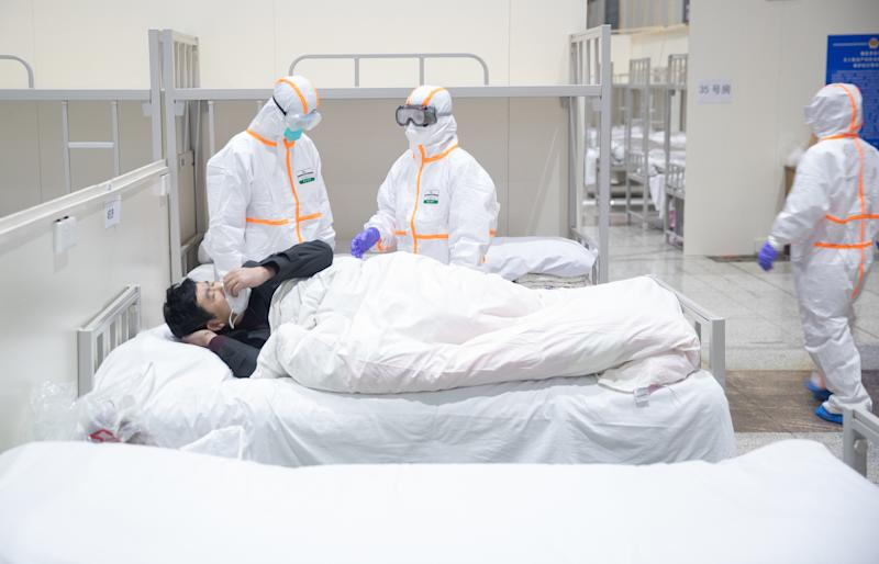 Chinese medical workers examine a patient infected with the new coronavirus and pneumonia at the newly-built Fangcang Hospital in Wuhan. Source: AAP