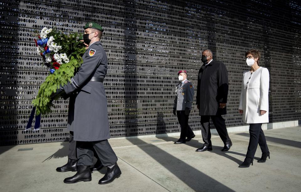 Annegret Kramp-Karrenbauer, Federal Minister of Defence, and U.S. Secretary of Defence Lloyd Austin lay down a wreath at the Federal Ministry of Defence in Berlin, Germany, Tuesday, April 13, 2021. This is the first visit to Germany by a minister of the new US administration. Austin will then travel on to Stuttgart, where he will talk to soldiers at the US command centres for troops in Africa and Europe. (Kay Nietfeld/dpa via AP)