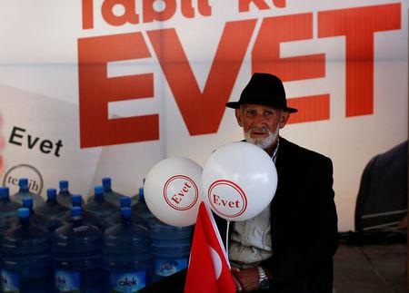 "An ""Evet"", ""Yes"" in English, supporter sits at a campaign point for the upcoming referendum in Istanbul"