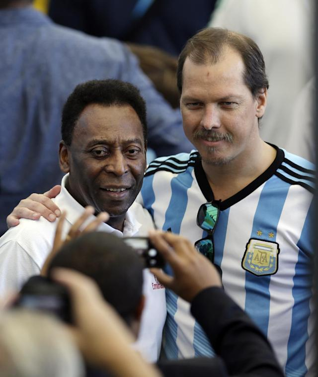 A man wearing a Argentine jersey has his picture taken with Brazilian soccer legend Pele before the World Cup final soccer match between Germany and Argentina at the Maracana Stadium in Rio de Janeiro, Brazil, Sunday, July 13, 2014. (AP Photo/Hassan Ammar)
