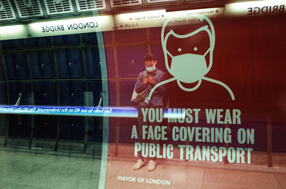 A man wearing a face mask, seen in reflection, waits for a Jubilee line service at London Bridge Station on the London Underground network in London, England, on October 15, 2020. London is to be placed under 'Tier 2' coronavirus lockdown measures from midnight on Friday, meaning 'high' alert for covid-19. Most notably the change will introduce a ban on people from different households from mixing anywhere indoors, prompting particular concern within the already badly-affected hospitality industry. (Photo by David Cliff/NurPhoto via Getty Images)