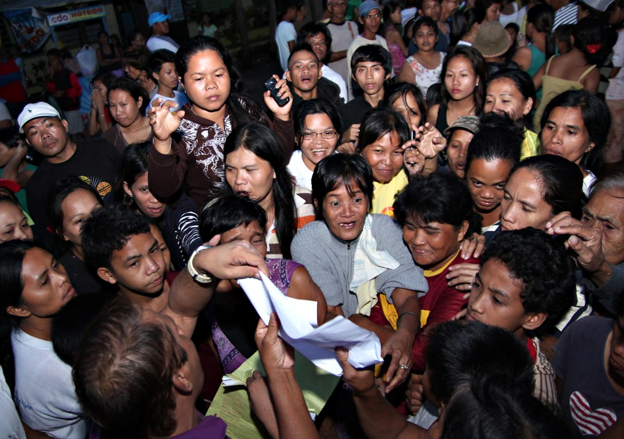 Residents gather to check the list of relief supplies at an evacuation center for typhoon victims in Butuan city in southeastern Philippines Tuesday, Dec. 4, 2012. Typhoon Bopha, one of the strongest typhoons to hit the Philippines this year, barreled across the country's south on Tuesday, killing dozens of people and forcing more than 50,000 to flee from inundated villages. (AP Photo/Erwin Mascarinas)
