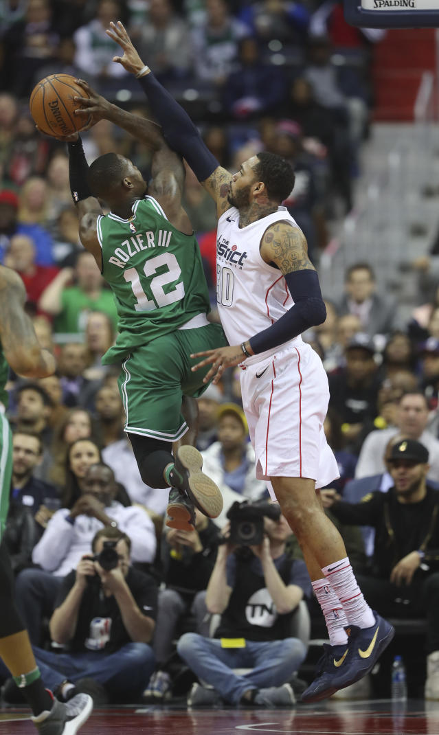 Boston Celtics guard Terry Rozier (12) is fouled while driving to the basket by Washington Wizards forward Mike Scott (30) during the first half of an NBA basketball game Thursday, Feb. 8, 2018, in Washington. (AP Photo/Pablo Martinez Monsivais)