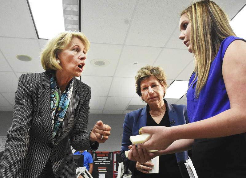 American Federation of Teachers President Randi Weingarten, center, listens as Education Secretary Betsy DeVos, left, talks to Van Wert High School freshman Alaina Arney about a patent she has applied for on a protective unit for a flush valve, during a visit to the Van Wert Robotics Club at Van Wert High School, Thursday, April 20, 2017, in Van Wert, Ohio. (Cathie Rowand/The Journal-Gazette via AP)