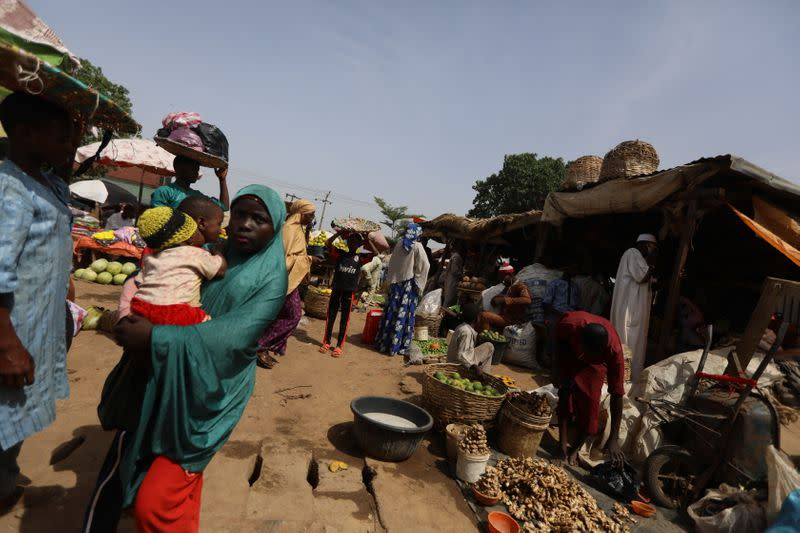 A man puts ginger plant bulbs in buckets at a market in Kaduna