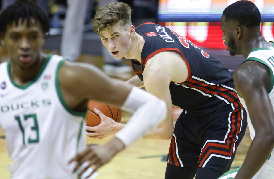 Utah center Branden Carlson (35) looks to pass against Oregon during an NCAA men's college basketball game in Eugene, Ore., Saturday, Feb. 20, 2021 (AP Photo/Thomas Boyd)