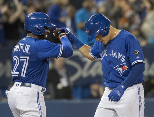 Toronto Blue Jays' Gio Urshela, right, celebrates with teammate Dwight Smith Jr. after hitting a two-run home run in the fifth inning of a baseball game against the Oakland Athletics in Toronto, Saturday, May 19, 2018. (Fred Thornhill/The Canadian Press via AP)