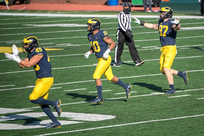 Adam Shibley (45) of the Michigan Wolverines, Anthony Solomon (10) of the Michigan Wolverines and Aidan Hutchinson (97) of the Michigan Wolverines celebrate after Michigan State Spartans missed a field goal during the fourth quarter at Michigan Stadium on Oct. 31, 2020, in Ann Arbor, Michigan.