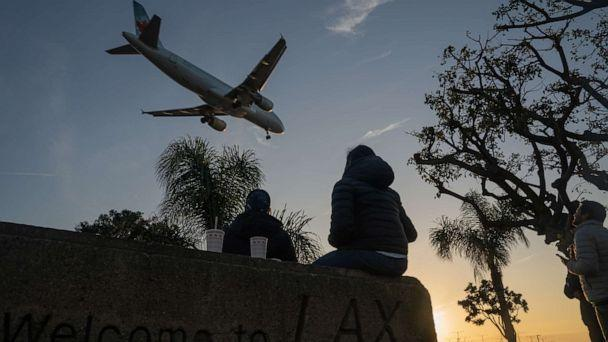 PHOTO: People watch an Air Canada Airbus SE A320 airplane land at Los Angeles International Airport (LAX) from a nearby park in Los Angeles, Nov. 23, 2020. (Bing Guan/Bloomberg via Getty Images, FILE)