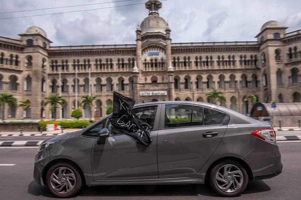 A convoy of cars with black flags are seen around Kuala Lumpur City Centre during a protest July 24, 2021. — Picture by Shafwan Zaidon