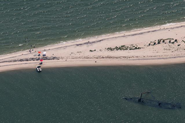 <p>Visitors swim in the waters along a sandbar on the south side of Tangier Island, Virginia, Aug. 2, 2017. (Photo: Adrees Latif/Reuters) </p>