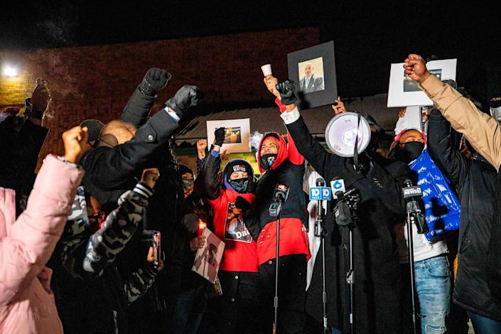 """A crowd raises their fists around Karissa Hill during a candlelight vigil for her father Andre Hill, an unarmed Black man who was shot and killed by a Columbus police officer, in Columbus, Ohio on Dec. 26, 2020.<span class=""""copyright"""">Stephen Zenner—AFP/Getty Images</span>"""