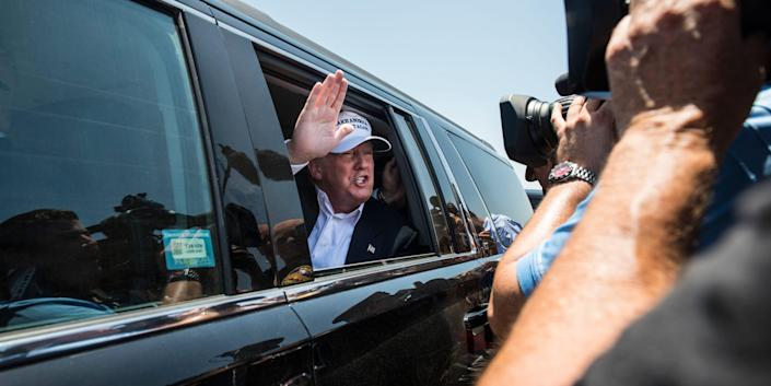 """Republican Presidential candidate and business mogul Donald Trump talks to media from his car wearing a, """"Make America Great Again,"""" hat during his trip to the border on July 23, 2015 in Laredo, Texas."""