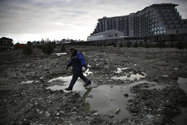 A construction worker steps over a puddle in a lot being prepared to be turned into a grassy lawn next to a newly built hotel across from the Olympic Park at the 2014 Winter Olympics, Thursday, Feb. 6, 2014, in Sochi, Russia. (AP Photo/David Goldman)