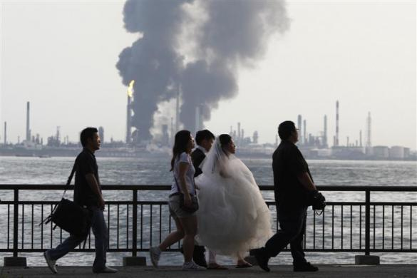A wedding couple and their photographers walk past the burning Pulau Bukom offshore petroleum complex of Royal Dutch Shell in Singapore September 28, 2011.