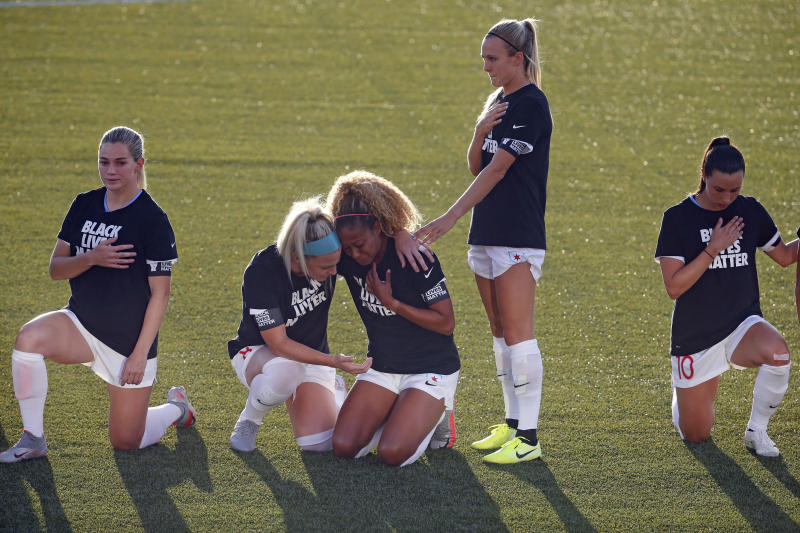 Casey Short (center) and Chicago Red Stars teammate Julie Ertz (second from left) share an emotional moment during the anthem on Saturday night. (AP Photo/Rick Bowmer)