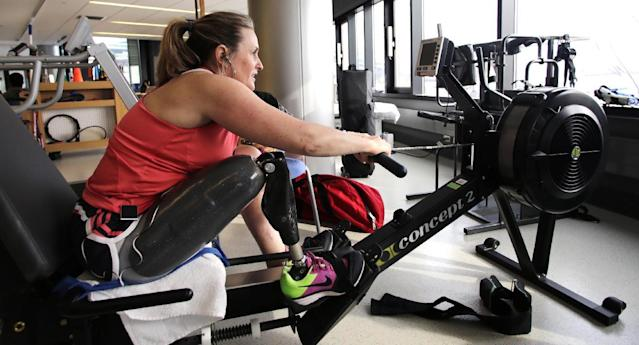In this Tuesday, March 11, 2014 photo, Boston Marathon bombing survivor Roseann Sdoia works out on a rowing machine at the Spaulding Rehabilitation Hospital in Boston. Sdoia goes to Spaulding twice a week for hour-long workouts with a physical therapist, and then she usually hops on the rowing machine to build her endurance after her therapy session. She aims to run again, a hobby she loved doing before her injury. (AP Photo/Charles Krupa)
