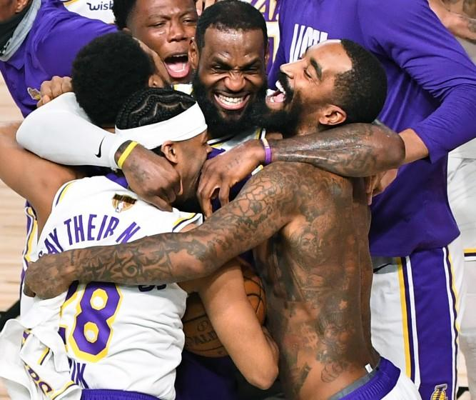 LeBron James, center, gives a group hug to several Lakers teammates, including a shirtless J.R. Smith
